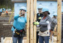 Habitat for Humanity volunteers work together framing a doorway.