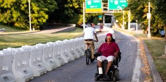 A woman wearing sitting in a motorized wheelchair smiles as she navigates her way up a temporary path in Baltimore.