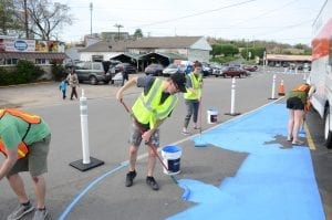 A group paints a blue temporary walking path.