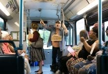 A woman, wearing a sign, stands and points a finger inside a bus.