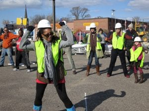 A group of people in yellow vests and hard hats dance.