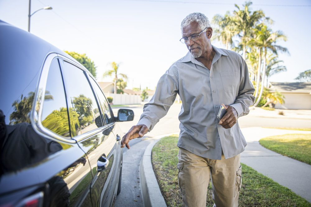 A senior black man uses a ride-hailing service and gets into the car that has arrived for him.