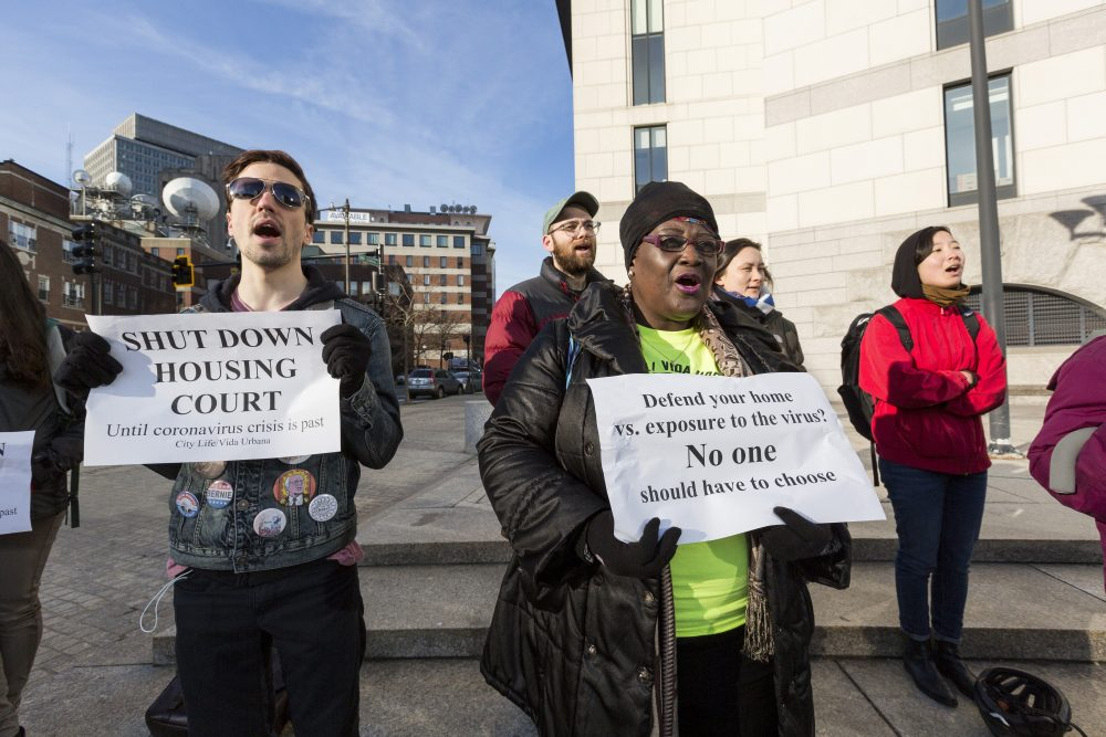 """A group of people stand three feet apart, mouths open as if shouting, outside a building that looks like a court. In the foreground a young white man in sunglasses with political buttons on his jacket holds a sign reading """"Shut down housing court until coronavirus is past."""" In the center, a Black woman with a neon yellow T-shirt and black jacket holds a sign reading """"Defend your home versus exposure to the virus? No one should have to choose."""""""