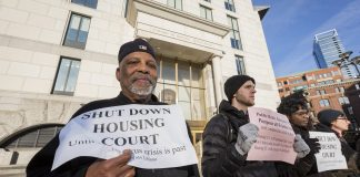 """A group of people stand in a line outside a building a court building. In the foreground Black man with a white beard in a black jacket and cap holds a sign a sign reading """"Shut down housing court until coronavirus is past."""""""