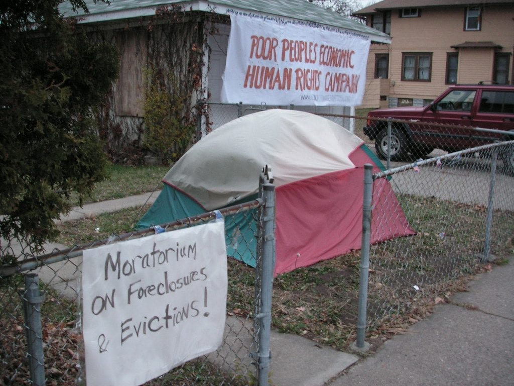 """A multicolored tent in a boarded-up house's front yard. A sign on the fence says """"Moratorium on foreclosures and evictions"""" and a sign on the house reads """"Poor People's Economic Human Rights Campaign"""""""