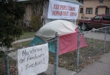 """A multicolored tent in house's front yard. A sign on the fence says """"Moratorium on foreclosures and evictions"""" and a sign on the house reads """"Poor People's Economic Human Rights Campaign"""""""