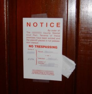 """A notice in red letters is taped to a wooden door. It reads """"Notice: by order of the [blanked out] County Special Civil Part. Tenants of these premises have been evicted and the plaintiff placed in full possession thereof. NO TRESPASSING."""""""