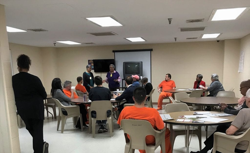 A group of jail inmates, some in orange shirts, sit at tables in a room while a woman talks with them about the history of voting rights. In the U.S.people who are jailed and awaitingtrialformisdemeanors or disenfranchisefelonies are legallyallowed to vote