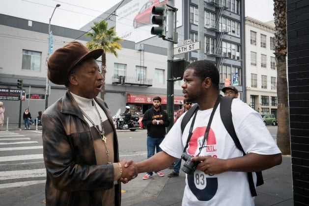 A man with a hat shakes the hand of a Visions of Justice student.