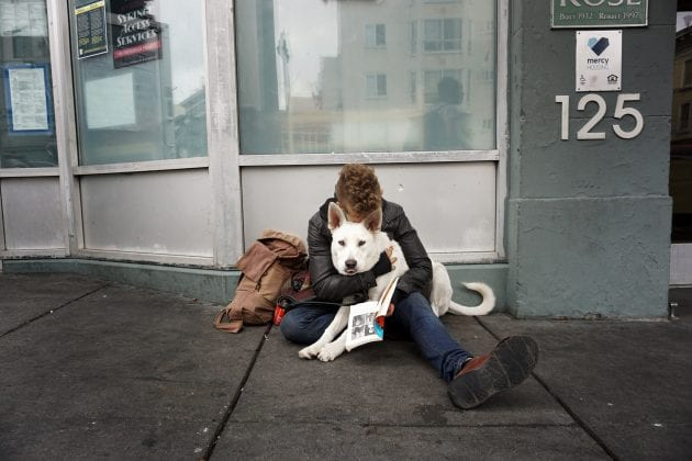 A person hugs a white dog on the streets.