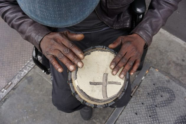 A photograph by Visions of Justice student Christopher Shurn. The image shows two hands hitting a drum with a black X on it.