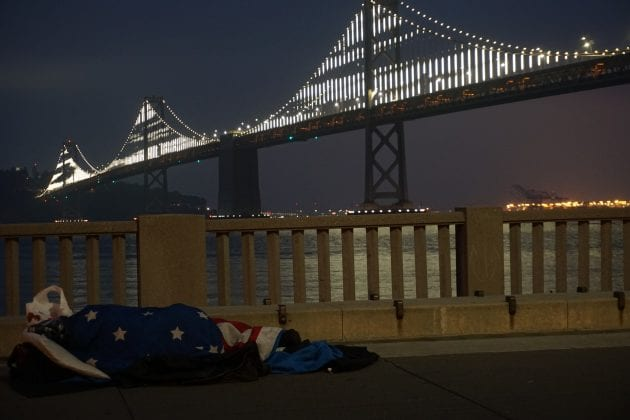 A person, drapped with the American flag, sleeps on the ground in front of a bridge at night.
