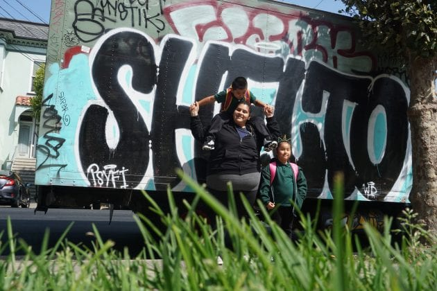 A woman stands in front of graffiti while holding a boy on her shoulders. A young child stands next to her.