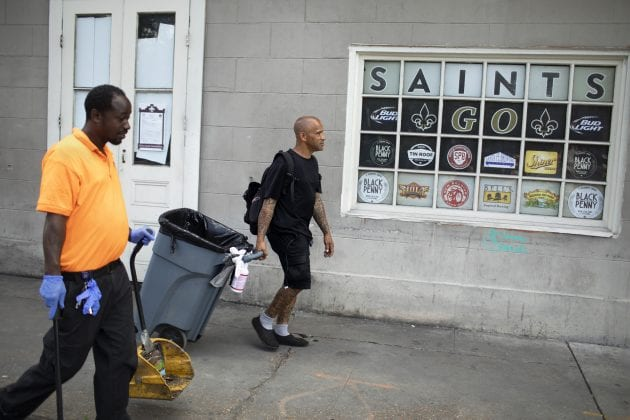 A man in black shorts and a black T-shirt pulls a garbage can on the sidewalk. Bobby Parker, an essential worker during the COVID-19 pandemic, was illegal evicted from his home for paying rent late.