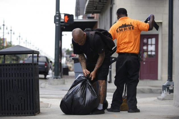 A man in black ties up a black garbage bag. He is a sanitation worker who was kicked out of his home during the pandemic for paying rent late.