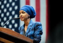 Rep. Ilhan Omar, who stands at a podium in front of an American flag, has proposed legislation that would cancel rents and individual mortgage payments nationwide to deal with the COVID-19 crisis.