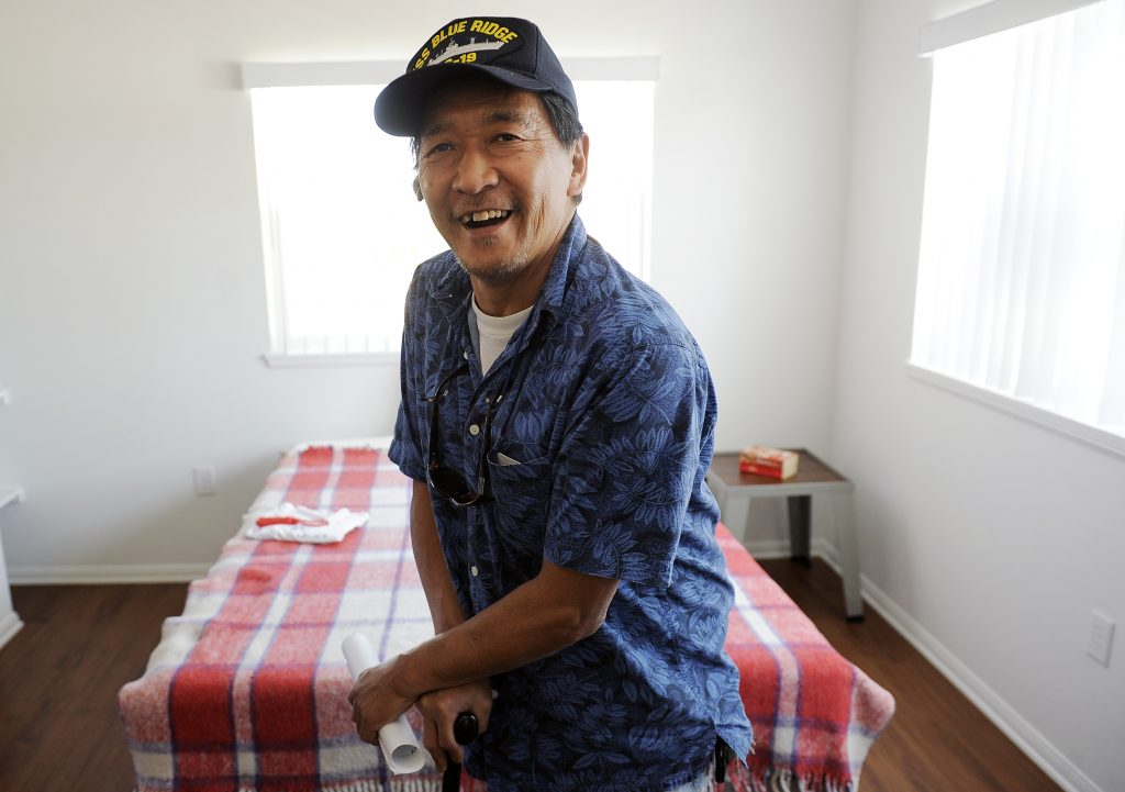 A man in a short sleeved blue button up shirt and a USS Blue Ridge baseball cap smiles at the camera, in front of a bed with a plaid red and white bedspread.