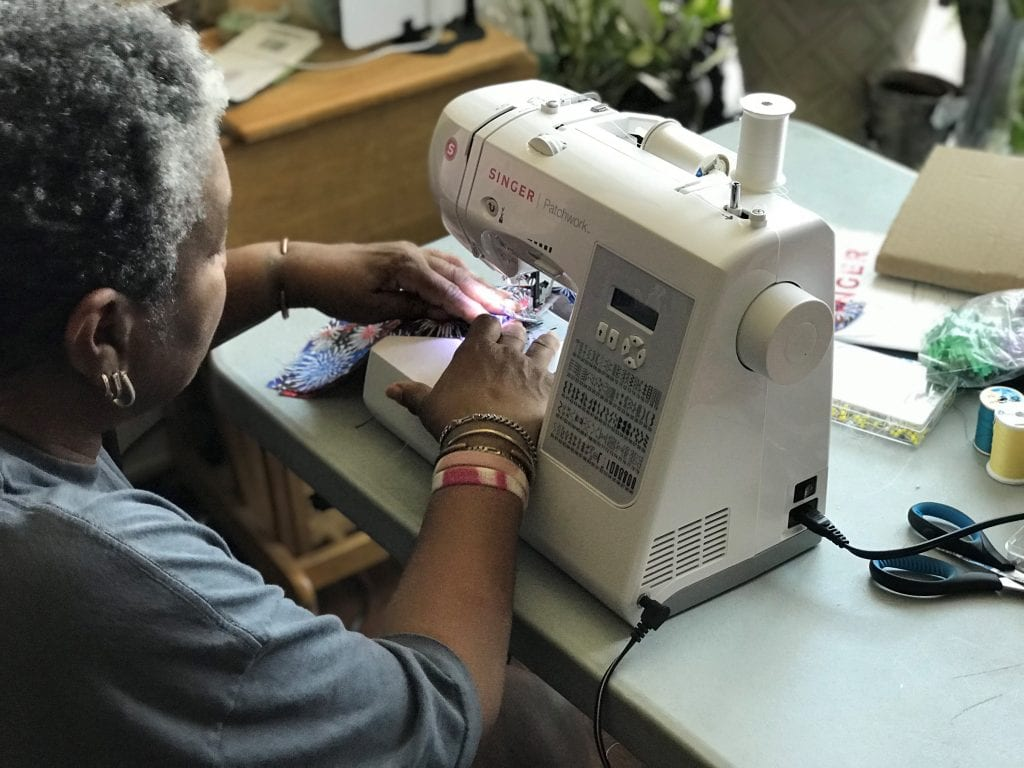 A woman on sews masks on a sewing machine