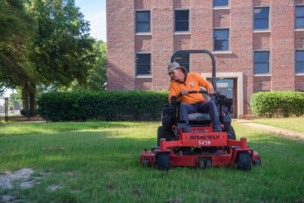 A man wearing a hat and a yellow shirt sits on a red lawnmower as he mows a lawn outside a large building. The man, who was formerly incarcerated, started a lawnmowing business.
