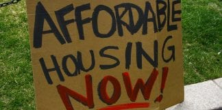"""homemade cardboard sign says """"Affordable Housing Now!"""""""