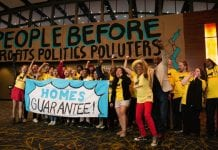 """A large group of cheering people wearing yellow T-shirts hold a sign that reads """"Homes Guarantee"""". In the background, a large sign reads """"People before profits, politics, polluters."""""""