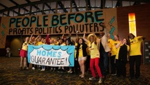 """Housing justice: A crowd of cheering people in yellow T-shirts holds a sign that reads """"Homes Guarantee"""". In the background, a large sign reads """"People before profits, politics, polluters."""""""