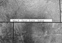 Tape sign on stone floor: Wait your turn here