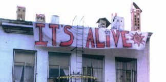 """Squatters occupy the Arion building in Seattle after it sat vacant for months. There are signs that read """"Operation Homestead"""" and """"It's Alive"""" outside the large white building."""