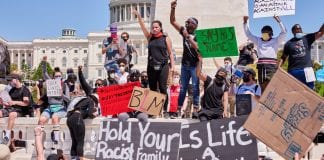 """Dozens of young people, mostly Black, gather with Capitol Hill in the background, holding signs that read """"Black Lives Matter."""" Two stand in the middle with arms upraised as if speaking to the crowd."""