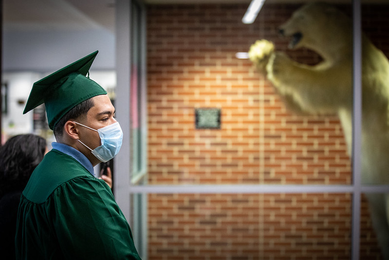 A young graduate wearing a green cap and gown and a mask waits for his name to be called. A white bear shows in the background. Graduates might face housing insecurity due to the coronavirus recession.