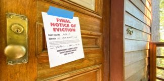 An eviction sign posted outside of a wooden door. Up to 23 million people could be evicted from their homes by September.