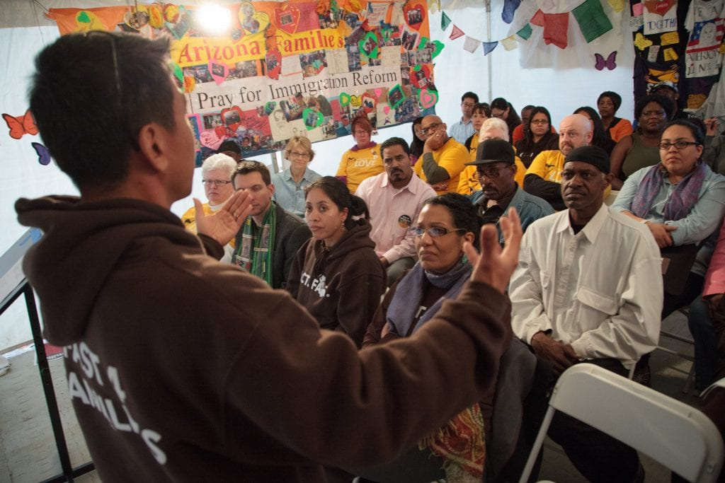 Man speaks in front of a crowd at a community meeting
