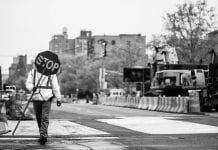 in New York, a person walks to the left holding a stop sign.
