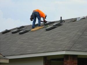 home repair: photo shows man in orange shirt repairing leak in roof