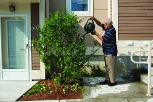 nonprofit housing: image shows man watering plant in front of nonprofit apartment building
