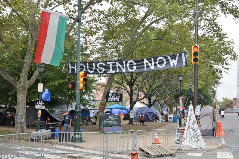 """Tents are lined up outside in Philadelphia. There are signs that read """"Housing Now!"""" and """"Black Lives Matter."""""""