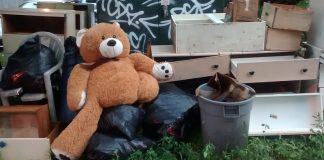 A teddy bear sits among discarded furniture on the side of the street