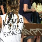 """Person at a protest wears a shirt that says, """"Acknowledge your privilege"""""""