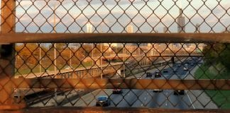 A view of the Chicago skyline through a rusty chain-link fence