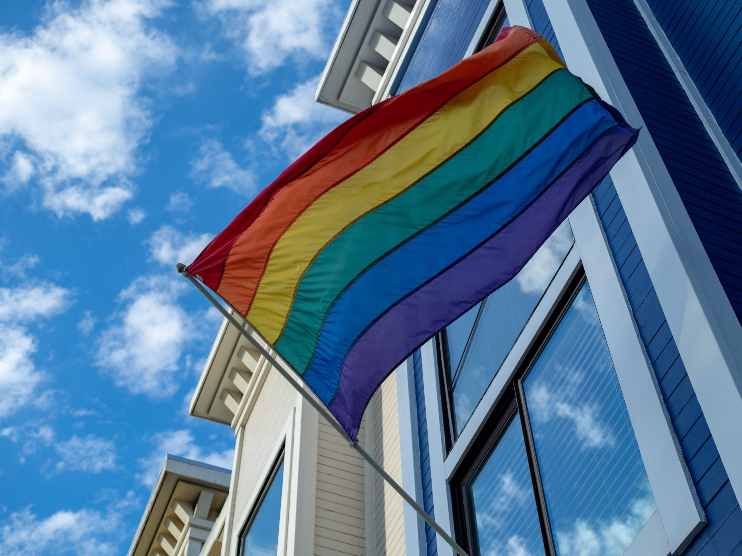 A rainbow flag waves outside of a window