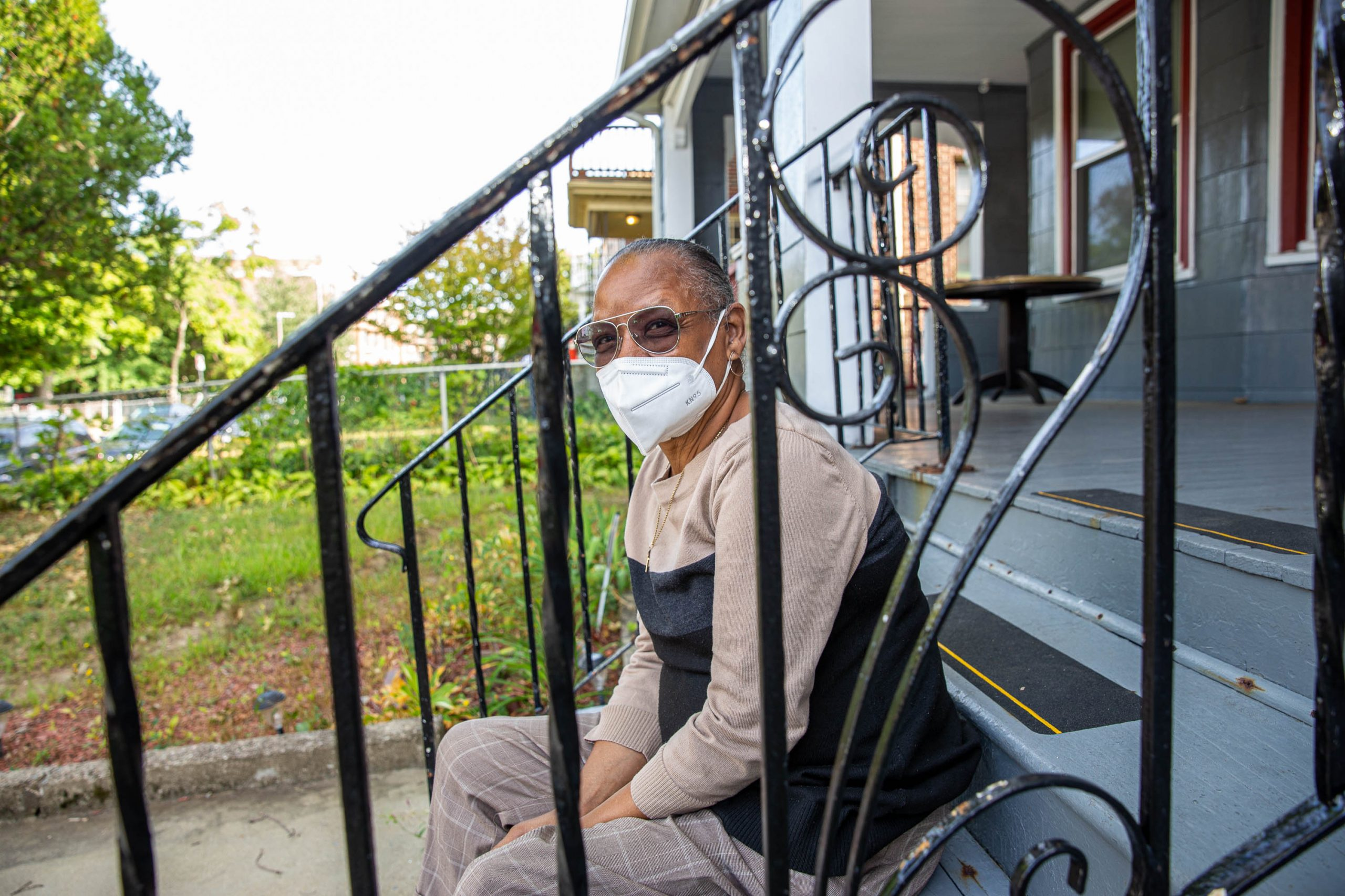 A person sits outside on the steps of their home. They were able to stay there because they received eviction diversion funds, or RAFT funding.