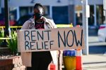 """A protestor holds a """"Rent Relief Now"""" sign during a North Carolina demonstration this month"""