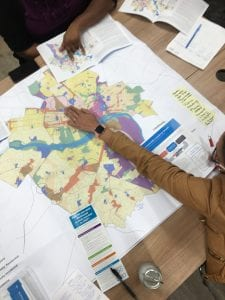 photo is view from above of hands pointing to maps as community engagement team discusses Richmond's future