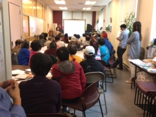 photos shows view from back of room at well-attended community meeting on in Chinatown, Boston.