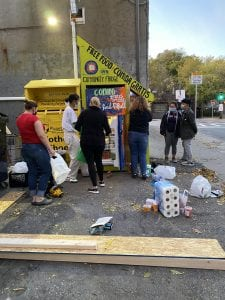 community fridge: image shows people getting food from an outdoor refrigerator