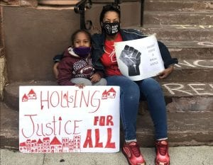 Emergency Services Grants. Photo shows a woman and her grandchild dremonstrating for housing court reforms in Albany, New York