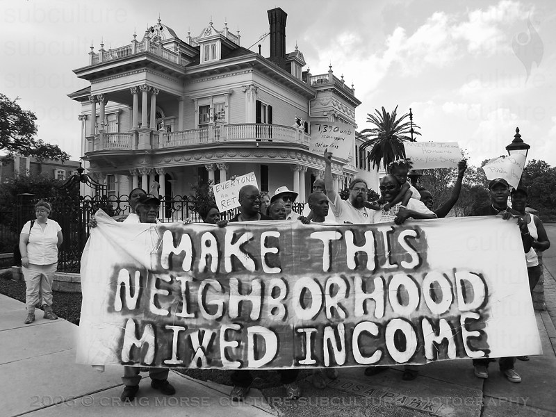 """photo shows a demonstration in New Orleans, with a sign reading """"Make this neighborhood mixed income"""""""