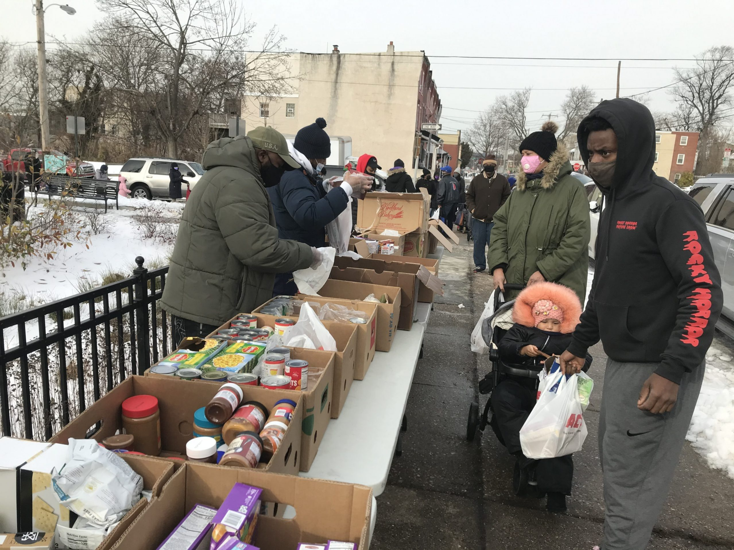 People stand in line to get food distributions on the street in Philadelphia.