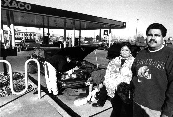 photo of two people standing near a Texaco gas station