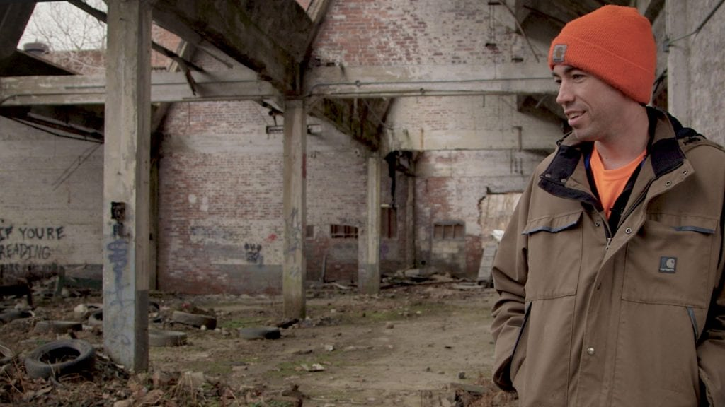 Still photo from The Place that Makes Us, a documentary about Youngstown, Ohio. Image shows a young man standing in a decrepit building with gaps in the roof.